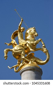Gold sculpture of St. George slaying a dragon atop a column in Freedom Square, Tbilisi, Georgia