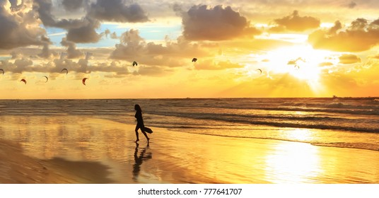 Gold sea sunset and kite surfing. Girl walks along the sea on wet sparkling sand, which reflects the evening sun. Panoramic view
