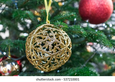 Gold Shiny Christmas Ornament hanging from a Green Pine Tree with Lights and a Red Ornament