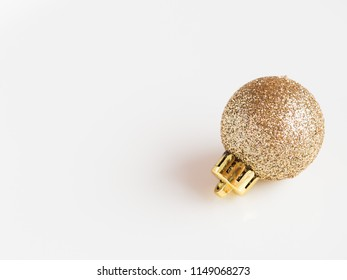 Gold shiny and flashy christmas ornament on a white background, traditional christmas decoration