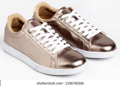 Gold shiny sneakers on white background.