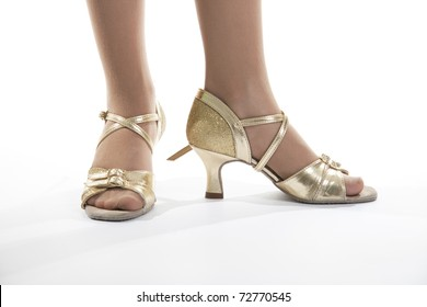 Gold shoes standing at the young dancer of the girl.  White background
