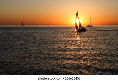 The gold silhouette of a sailing boat