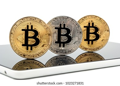 Gold and silver bitcoin coin on tablet close up