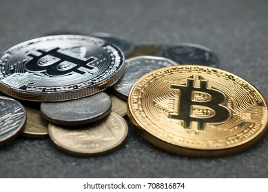 Gold and silver bitcoin coins against a black background.