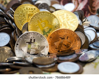 Gold, Silver and Bronze Bitcoin crypto currency coins among large stack of coins
