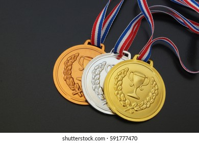 Gold, silver and bronze medal with ribbons on black board