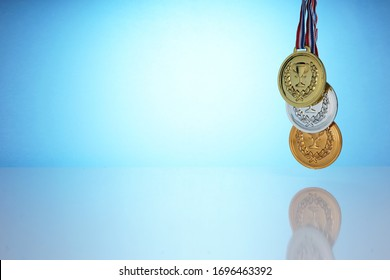 The gold, silver and bronze medal is a symbol of reward in every competition. The champion holds a colections of medal in his hand.