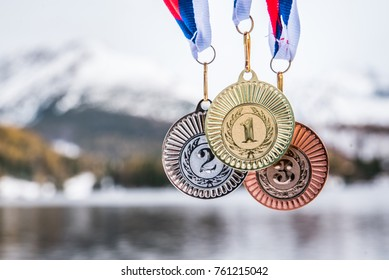 Gold, silver and bronze medal with winter nature in background. Sport trophy concept photo for winter game in South Korea