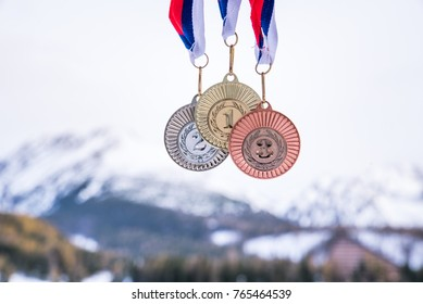 Gold silver and bronze medal with winter mountains in background. Sport trophy photo