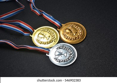Gold, silver and bronze medals on top of black board