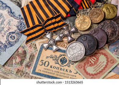 Gold and silver coins of the Russian Empire19 - 20 century in the background kopyur.Five rubles Nicholas II.Concept Russian antiques.Saint George cross of Imperial Russia.Antikvariat.