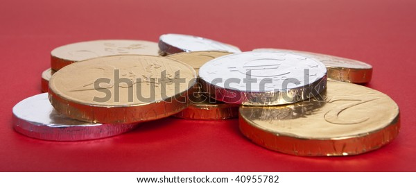 Gold and silver foil wrapped chocolate euro's against red background with shallow focus.