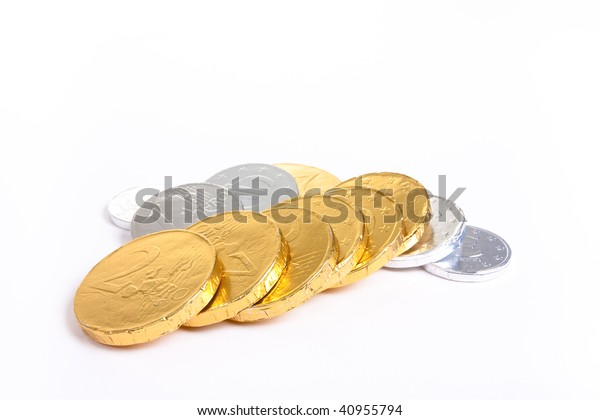 Gold and silver foil wrapped chocolate euro's against white background with shallow focus.