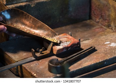 gold and silver granules in a  crucible for melting an alloy, jewelry tools in a goldsmith workplace, copy space, selected focus