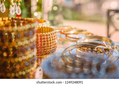 Gold and Silver jewllery displayed on a glass table in the window
