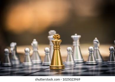 Gold and silver King and Knight of chess battle on board . Gold king are leader to fight with teamwork to victory.  Leader and teamwork concept for success.