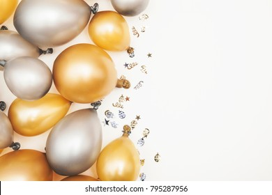 Gold and silver party celebration balloons on a plain background