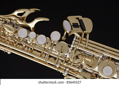 A gold and silver soprano saxophone isolated against a black background.