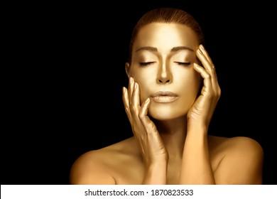 Goldene Hautfrau. Schöne sinnliche junge Frau mit leuchtendem metallischem goldenem Körper, die sich die Hände anmutig auf ihr Gesicht hebt, mit geschlossenen Augen einzeln auf schwarzem Hintergrund