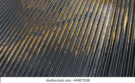 Gold in the Sluice Box - A close-up image of placer gold captured in the riffles of a black sluice box