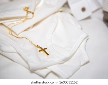 Gold small holy orthodox christening cross resting on a newborn  infant clothing during christening.