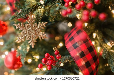 Gold snowflake ornament with buffalo plaid ribbon on Christmas tree