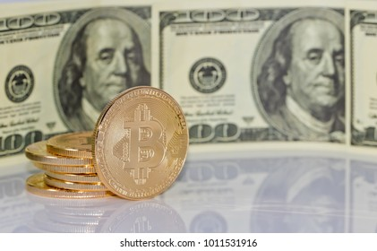 Gold souvenir coin bitcoin and a hundred-dollar bill lying on black reflective surface