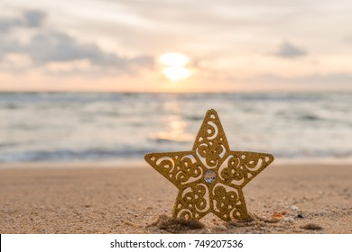 Gold star decorations on the sand of tropical ocean beach , happy New Year and Merry Christmas holidays travel destinations concept