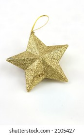 Gold star shaped Christmas decoration on a white background