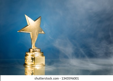 gold star trophy in smoke, blue background