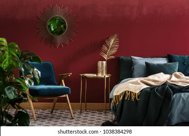 Gold table between green armchair and bed in sophisticated red bedroom interior with mirror