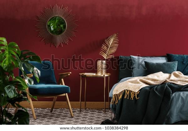 Table dorée entre fauteuil vert et lit dans une chambre rouge sophistiquée à l'intérieur avec miroir