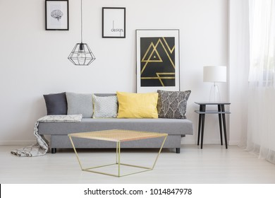 Gold table in front of a gray couch with black, white and yellow cushions in simple living room interior