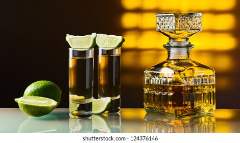 gold tequila and lime on a glass table.
