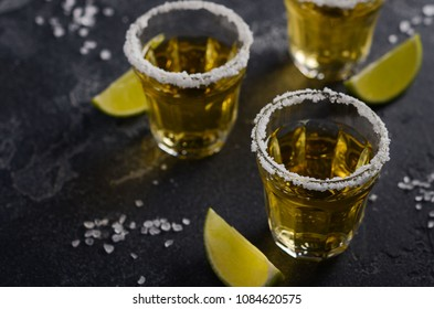 Gold tequila with lime and salt rim on dark stone or concrete background, selective focus