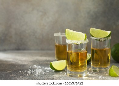 Gold Tequila. Mexican Gold Tequila shot with lime and salt on a stone light concrete worktop. Copy space.