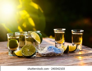 gold tequila with salt and lime on old wooden table.