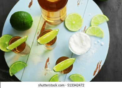 Gold tequila shots with lime and salt on gray table