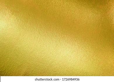 Arrière-plan de la texture dorée avec éclat brillant de luxe jaune brillant brillant de reflets lumineux sur la surface dorée, pour toile de fond de célébration, papier peint, fond de décoration de Noël ou tout design