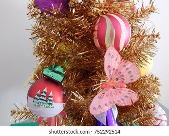A gold tinsel Christmas tree adorned with colorful festive baubles including party whistles and a pink butterfly..