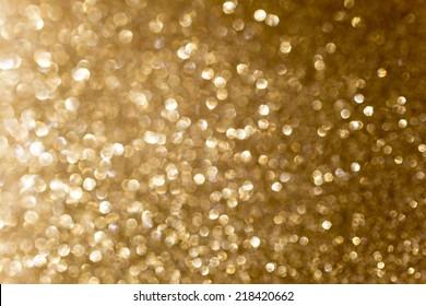 Gold tone background of defocused glittering lights.