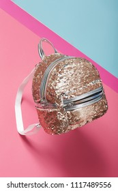 A gold tone mermaid scale backpack isolated against the bright pink and blue background. The fashionable lady's accessory featuring iridescent sequins, a top handle, a front pocket, a zipper closure.