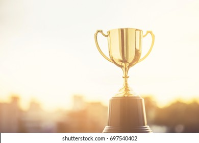 A gold trophy cup for champion with sunset sky background. Copy space ready for your design. Concept for winning and the best in a business.