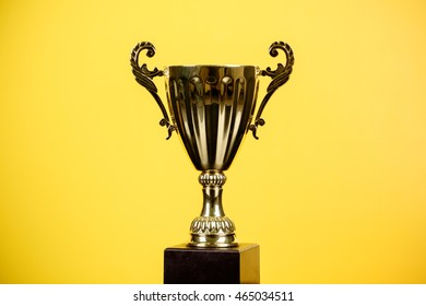 Gold trophy over yellow background