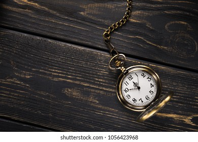 Gold vintage pocket watch on a wooden table. Old time background. Top view