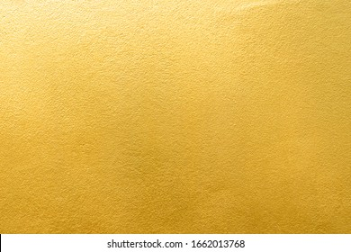 Gold wall texture background. Yellow shiny gold foil paint on wall surface with light reflection, vibrant golden luxury wallpaper