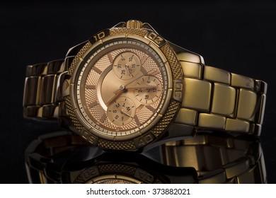 Gold watch on a monochrome plastic background, studio lighting, Macro