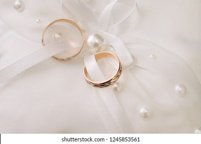 Gold wedding engagement rings on the pincushion close-up view from the top