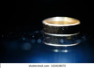 Gold wedding ring on black glass